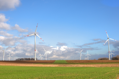 Sunny countryside in Belgium with wind turbines.
